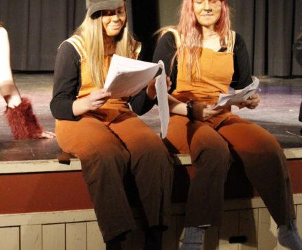 Nuorisoteatterin kaksi näyttelijää istumassa teatterin lavalla.