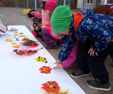 lapset pihalla tekemässä luontotaidetta