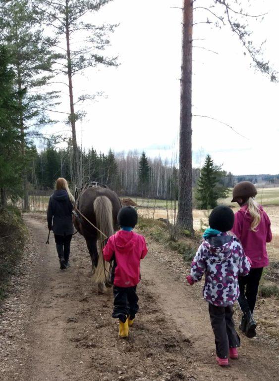 Heppakerholaiset kävelyllä metsätiellä. Yksi lapsista ohjaa ponia.