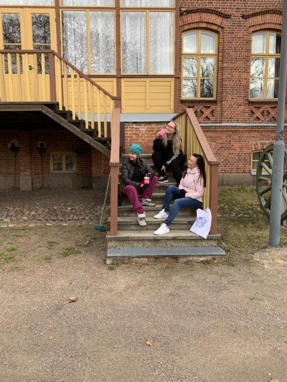 Jenny, Sanna ja Marjut istumassa ulkorappusilla.