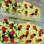 Salaatti, jossa kurkkuviipaleita ja minitomaateista sekä oliiveista tehtyjä leppäkerttuja.