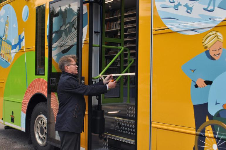 Hannu Muhonen leikkaamassa nauhaa kirjastoauton ovella.