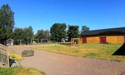 Takapihalla nurmialue ja hiekkatie. Piha rajautuu keltaisiin rakennuksiin.