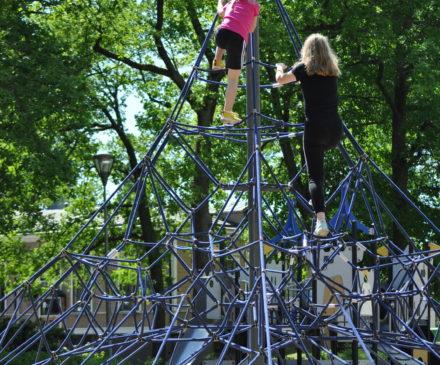 Leikkipuiston kiipeilytelineessä kaksi tyttöä.