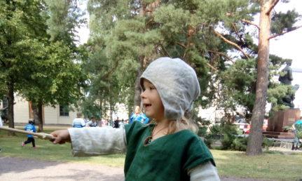 Lapsi puumiekka ja -kilpi kädessään nurmikolla.