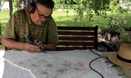 Taiteilija tekemässä kivipiirrosta puutarhassa.