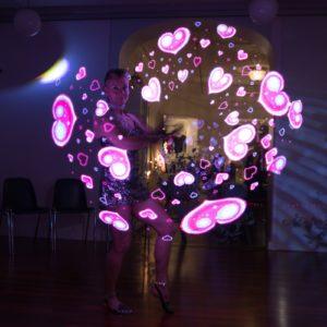 Firelady tekemässä valoshowta, jossa sydämiä pallon muodossa.