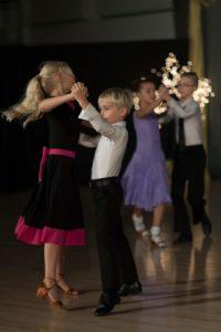 Havestepin tanssijat, pitkä tyttö mustassa mekossa ja pinkissä koristeissa ja poika mustissa housuissa ja valkoisessa paidassa.