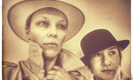 Seepiakuva, jossa kaksi hattupäistä esiintyjää.
